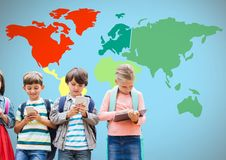 Kids on devices in front of colorful world map. Digital composite of Kids on devices in front of colorful world map Royalty Free Stock Images