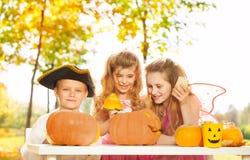 Kids in different costumes craft Halloween pumpkin Stock Photo
