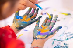 Kids dirty painted hand in art classroom. Kids with dirty painted hand in art classroom royalty free stock photography