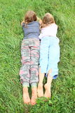 Kids with dirty soles of bare feet. Dirty soles of bare feet of two little girls - kids lying on green grass stock image