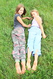 Kids with dirty soles of bare feet. Dirty soles of bare feet of two little girls - smiling kids lying on green grass Stock Images