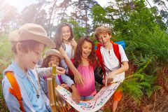 Kids discussing map during summer navigation game. Group of happy children boys and girls with treasure hunt game map discussing route in forest learning royalty free stock photography