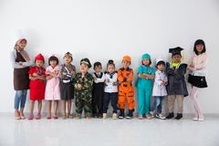 Kids with diverse multi profession uniform. Group of kids with diverse multi profession uniform on white background together royalty free stock photo