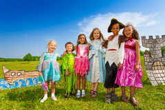 Kids diversity in costumes stand close and hug Stock Photo