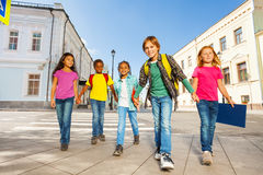 Kids diversity walking together holding hands Stock Photos