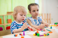 Kids doing arts and crafts. Children in kindergarten. Royalty Free Stock Images