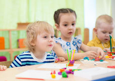 Kids doing arts and crafts in day care centre Stock Photos