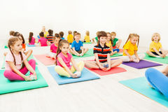 Kids doing butterfly exercise sitting on yoga mats. Portrait of 5-6 years old boys and girls doing butterfly exercise sitting on yoga mats in gym Royalty Free Stock Images