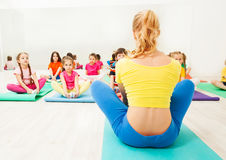 Kids doing butterfly stretch with female coach