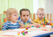 Kids doing cake in day care centre stock photos