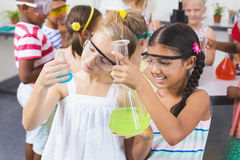 Kids doing a chemical experiment in laboratory. At school Royalty Free Stock Photo
