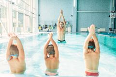 Kids doing exercise in swimming pool. With hands up. Instructor shows an exercise for children. Healthy sports activity in pool. Sportive kids activity in Stock Photos