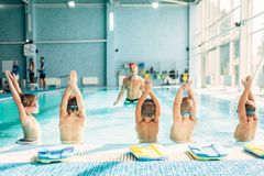 Kids doing exercise in swimming pool. With hands up. Instructor shows an exercise for children. Healthy sports activity in pool. Sportive kids activity in Stock Image