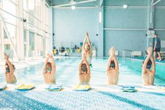 Kids doing exercise in swimming pool. With hands up. Instructor shows an exercise for children. Healthy sports activity in pool. Sportive kids activity in Royalty Free Stock Photo