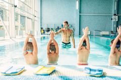 Kids doing exercise in swimming pool. With hands up. Instructor shows an exercise for children. Healthy sports activity in pool. Sportive kids activity Royalty Free Stock Image