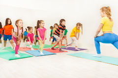 Kids doing gymnastic exercises in fitness class. Group of happy six years old kids and female instructor doing gymnastic exercises in fitness class Royalty Free Stock Photo