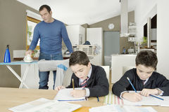 Kids doing homework, dad ironing. Stock Images