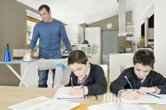 Kids doing homework, dad ironing. stock images