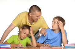 Kids doing homework with father stock image