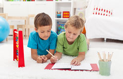 Kids doing math exercises on the floor Royalty Free Stock Photo