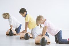 Kids doing resuscitation. Training on medical dummy during first aid course royalty free stock images