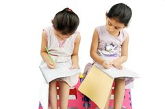Kids doing their homework, over white. Stock Photo