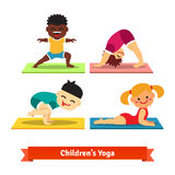 Kids doing yoga poses on colorful mats Royalty Free Stock Image