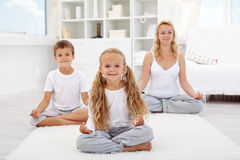Kids doing yoga relaxing exercise Royalty Free Stock Photos