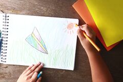 Kids draw rockets and sun onto white paper.
