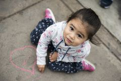 Kids Drawing with Chalk on Sidewalk royalty free stock images