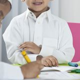 Kids drawing with colored crayons at a table royalty free stock photos