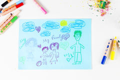 Kids drawing of family and colored pencils on wooden table Royalty Free Stock Photo
