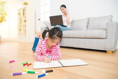 Kids drawing and mother working. Kids girl lying down on wooden floor drawing on sketchbook and mother working with computer talking on the phone on background Stock Photos