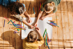 Kids drawing on paper with pencils while lying on floor. Cute kids drawing on paper with pencils while lying on floor Stock Images