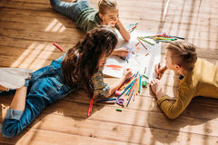 Kids drawing on paper with pencils while lying on floor. Cute kids drawing on paper with pencils while lying on floor Royalty Free Stock Images