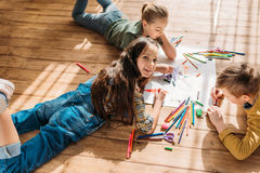 Kids drawing on paper with pencils while lying on floor. Cute kids drawing on paper with pencils while lying on floor royalty free stock image