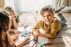 Kids drawing on paper with pencils while lying on floor. Cute kids drawing on paper with pencils while lying on floor stock photo