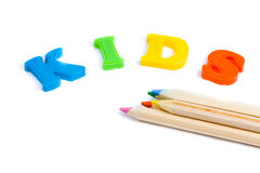 Kids and drawing pencils. Studio shot of plastic letters forming the word Kids and some color pencils, isolated on white background Stock Photos