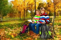 Kids drawing sitting on the bench in the park Royalty Free Stock Photos