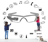 Kids drawing a wearable glasses applications chart. On the wall royalty free stock photos