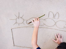 Kids draws picture on Sand Beach Summer holiday background Stock Images