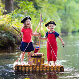 Kids playing pirate adventure on wooden raft. Kids dressed in pirate costumes and hats with treasure chest, spyglasses, and swords playing on wooden raft sailing stock images