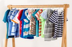 Kids dressing closet with clothes arranged on hangers. stock photos