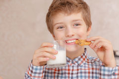 Kids drink milk and biscuits Royalty Free Stock Images