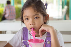 Kids are drinking fruit smoothies. Kids sit on chair is drinking fruit smoothies Royalty Free Stock Photography