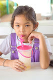 Kids are drinking fruit smoothies. Kids are drinking fruit smoothies on white table Royalty Free Stock Photo