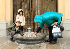 Kids drinking medicinal spring. Korean kids - boy and girl - and adult filling and drinking medical water in promenade 'Mlynska kolonada' (Mill colonnade) from Royalty Free Stock Photography