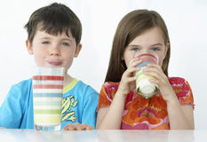 Kids Drinking Milk From Colorful Glasses Royalty Free Stock Images