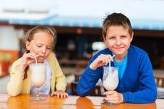 Kids drinking milkshakes. Kids brother and sister drinking milkshakes in outdoor cafe royalty free stock image