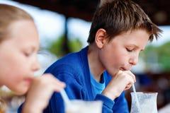 Kids drinking milkshakes. Kids brother and sister drinking milkshakes in outdoor cafe Royalty Free Stock Images